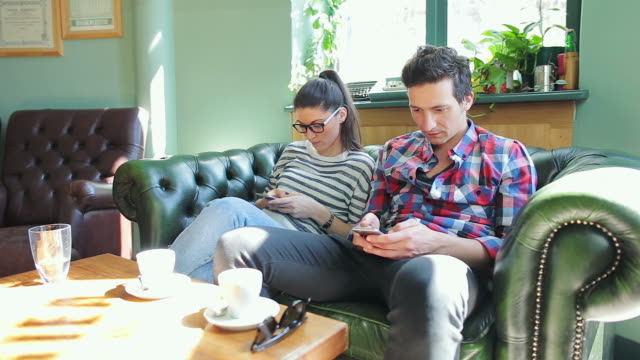 young people browsing their smart phone in coffee shop. - communication problems stock videos & royalty-free footage