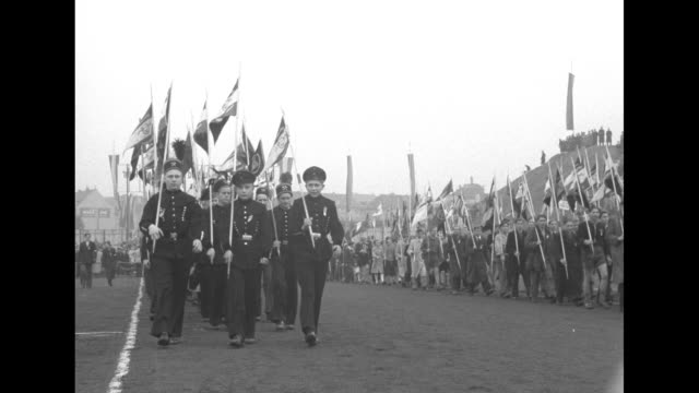VS young people carrying scores of flags in Walter Ulbricht Stadium some marchers with crossed hammer and chisel insignias on hats