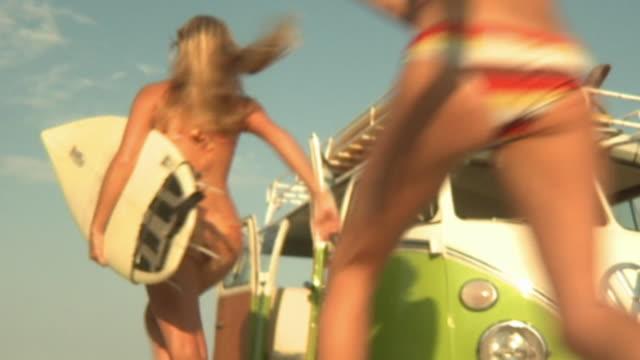 slo mo ms la young people carrying surfboards running past van towards beach, jacksonville, florida, usa - van stock videos & royalty-free footage