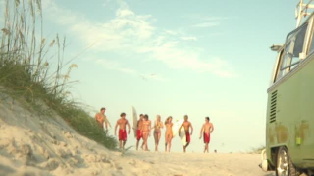 slo mo ms la young people carrying surfboards walking on beach, jacksonville, florida, usa - ビキニ点の映像素材/bロール