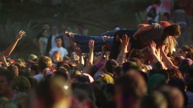 vídeos de stock, filmes e b-roll de young people covered in colored powder and celebrating - jogando se na multidão