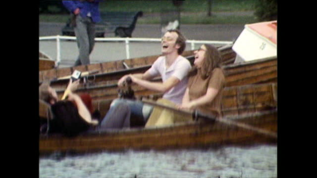vídeos de stock e filmes b-roll de young people crash their rowing boat on serpentine lake; 1971 - imagem múltipla