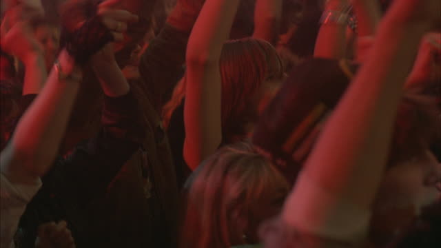Young people dancing and keep beat to the music at a rock-and-roll concert.