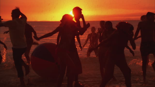 MS ZI Young people dancing at beach in silhouette against sunset