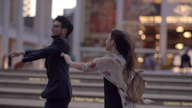 vidéos et rushes de young people dancing excited in the city having fun together. urban lifestyle scene of asian man and caucasian women - plan en travelling