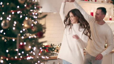 vídeos de stock e filmes b-roll de young people dancing next to the christmas tree. they cheerfully and joyfully celebrate christmas. - fairy lights
