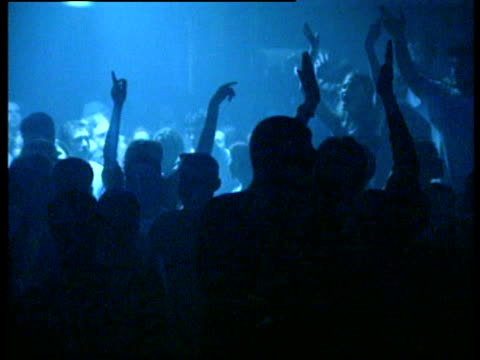 vídeos de stock e filmes b-roll de young people dancing rave style under flashing lights and strobes at nightclub - luz estroboscópica