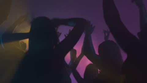 vídeos de stock, filmes e b-roll de hd: jovens dançar com os braços para cima - discoteca