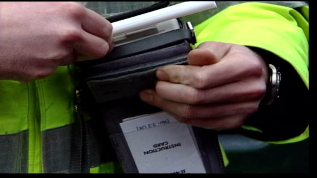 dangers of alcohol file / tx police officer preparing breathalyser / man blowing into breathalyser - alkoholtest stock-videos und b-roll-filmmaterial