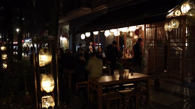 young people eat in the evening in schlesische strasse in district friedrichshain-kreuzberg during the second wave of the coronavirus pandemic on... - nachtleben stock-videos und b-roll-filmmaterial