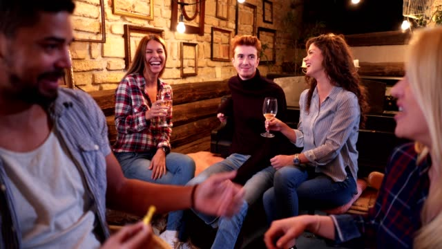 Young people enjoying drinks at a house party
