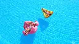 AERIAL SLOW MOTION TOP DOWN: Young people enjoying on pizza and flamingo floats