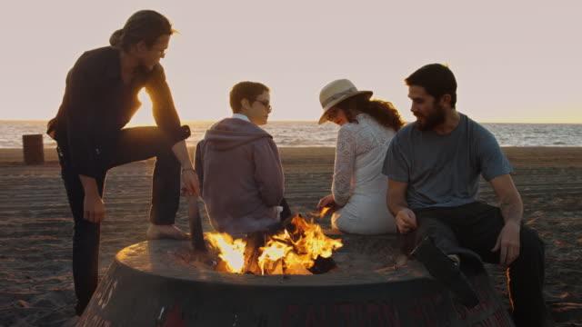 junge leute hängen out am strand-lagerfeuer - in den dreißigern stock-videos und b-roll-filmmaterial