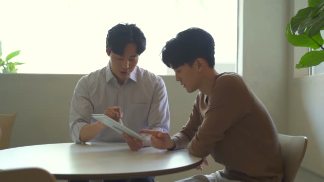 young people having a meeting with a tablet pc, startup business - 人間の鼻点の映像素材/bロール