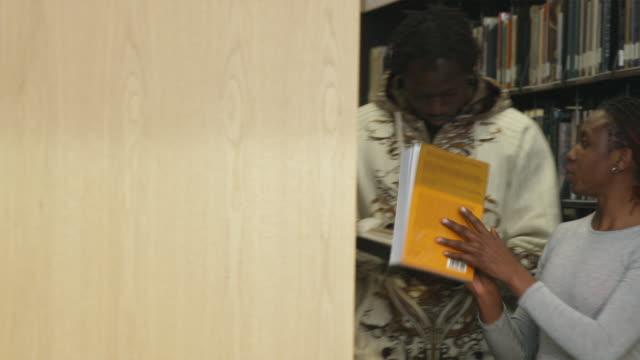 vídeos y material grabado en eventos de stock de ms pan young people in between books shelves at library, orem, utah, usa - orem