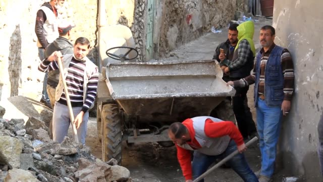 young people in mosul clear rubble from the streets with using small vehicles to remove debris through the narrow streets of the city that was... - rebuilding stock videos and b-roll footage