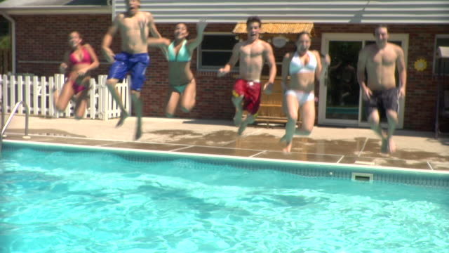 ms, young people jumping into swimming pool together, middlesex, new jersey, usa - wet hair stock videos & royalty-free footage