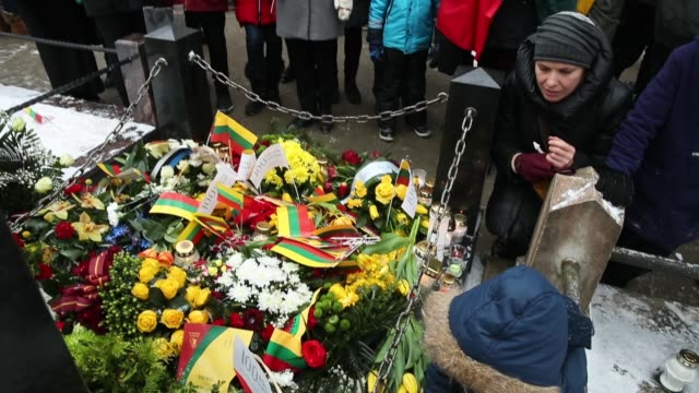 Young people lay candles and flags at the grave of Lithuanian National Revival activist Jonas Basanavicius at Rasos Cemetery during the 100th...