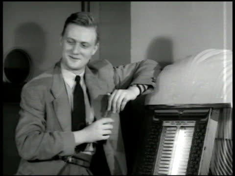 young people listening to jukebox man leaning on jukebox. woman looking at records in apartment. man turning to his phonograph player. portable... - 1949 bildbanksvideor och videomaterial från bakom kulisserna