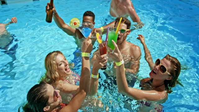 SLO MO Young people making a toast while in the pool at a party