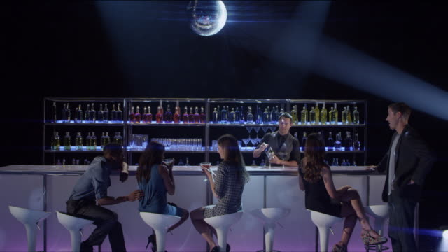 ws young people mingle at nightclub bar as bartender makes and serves drinks - bar stock videos & royalty-free footage