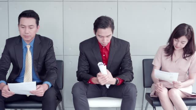 vidéos et rushes de young people of all ages are unemployed sitting in a chair holding a job application queuing for a job interview. - petite annonce