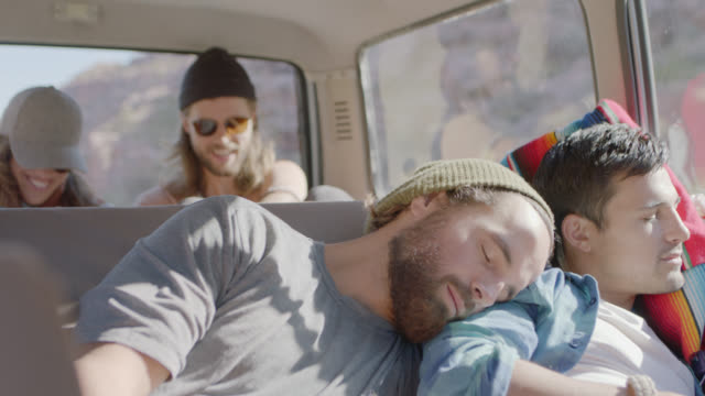 vídeos y material grabado en eventos de stock de young people on road trip talk and laugh in backseat of car as two male friends nap on each other. - asiento de atrás