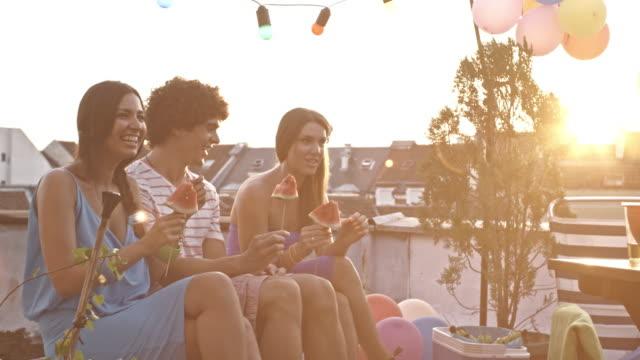 junge menschen auf dem dach partei, wassermelone essen - kühlbehälter stock-videos und b-roll-filmmaterial