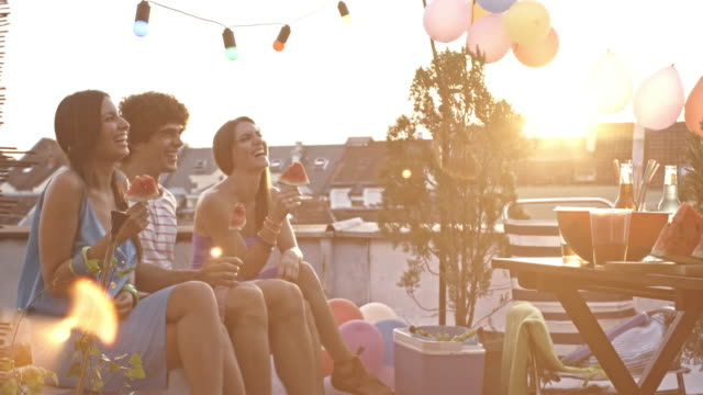 vídeos de stock e filmes b-roll de young people on rooftop party, eating watermelon - lanche
