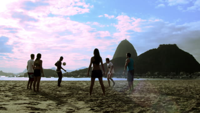vidéos et rushes de young people play soccer in front of sugar loaf mountain, in rio de janeiro - petit groupe d'animaux