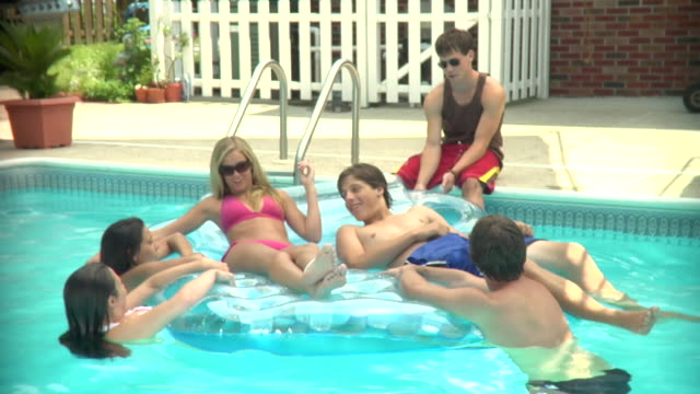 vidéos et rushes de ms, young people relaxing on mattress in swimming pool, middlesex, new jersey, usa - 16 17 ans