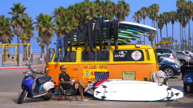 Young people renting surfing equipment to the tourists in Venice Beach, Los Angeles, California, 4K