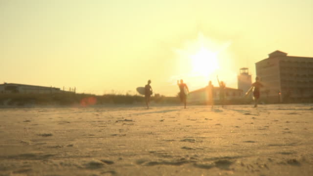 ws la young people running with surfboards on beach at sunset, jacksonville, florida, usa - low angle view stock videos & royalty-free footage