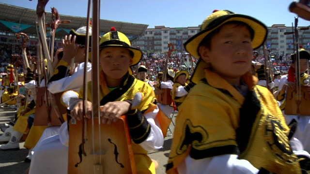young people sitting and holding their morin khuurs string instruments at naadam festival - モンゴル点の映像素材/bロール