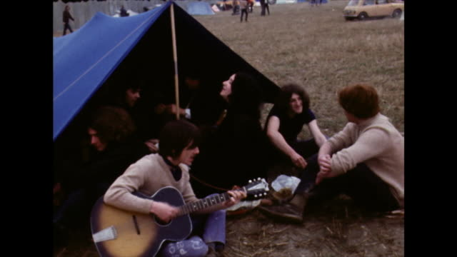 young people sitting and playing music at festival; 1970 - cross legged stock videos & royalty-free footage