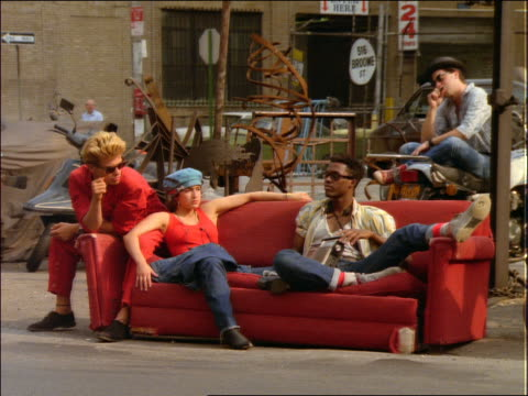 Young people sitting on couch on sidewalk / NYC