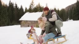 SLO MO Young people sliding down the hill and a couple on the snow sled falls down laughing