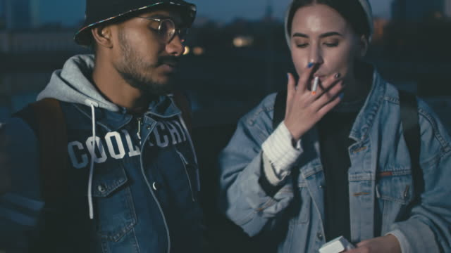 young people smoking and dancing outdoors - thema rauchen stock-videos und b-roll-filmmaterial