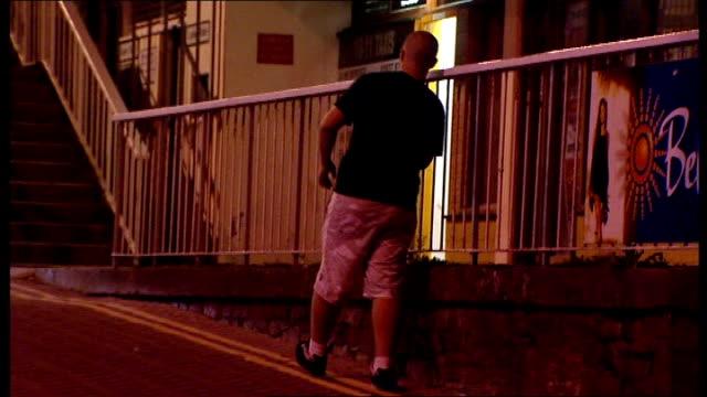 Young people staggering drunkenly away on street Drunken youth using railings to help himself walk along Drunken teenager slumped over wall Teenagers...