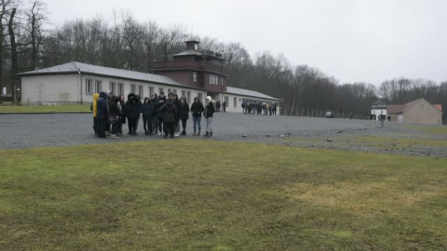 young people stand in front of the former main entrance to the buchenwald concentration camp on january 26 2018 near weimar germany tomorrow january... - campo di concentramento di buchenwald video stock e b–roll