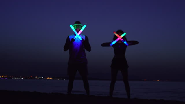 young people standing with glowing sticks at night - luce led video stock e b–roll