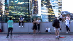 young people taking pictures of each other on the background of modern buildings, time lapse