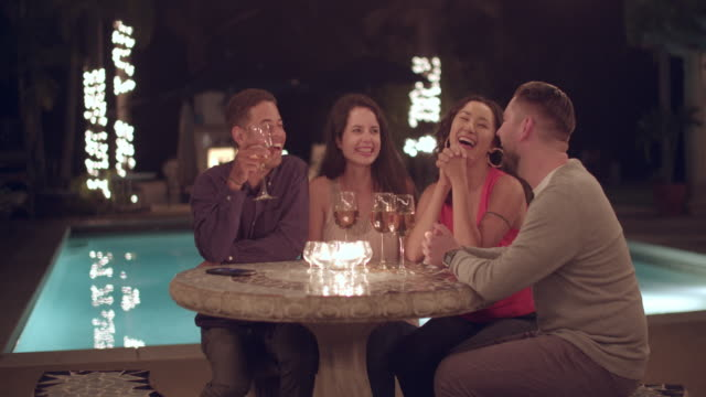 vidéos et rushes de young people talking by a swimming pool at night - rebord de piscine