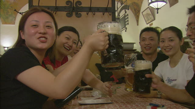 cu young people toasting with beer at table in hofbrauhaus, munich, bavaria, germany - beer stein stock videos and b-roll footage