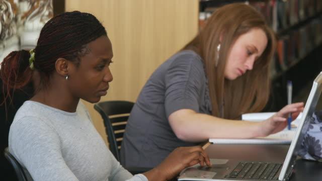 vidéos et rushes de cu ds young people using laptop and reading at library, orem, utah, usa - orem