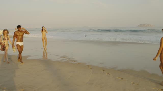 vídeos de stock e filmes b-roll de rio de janeiro-june 16: young people walk along the beach on june 16, 2013 in rio de janeiro. - fato de banho