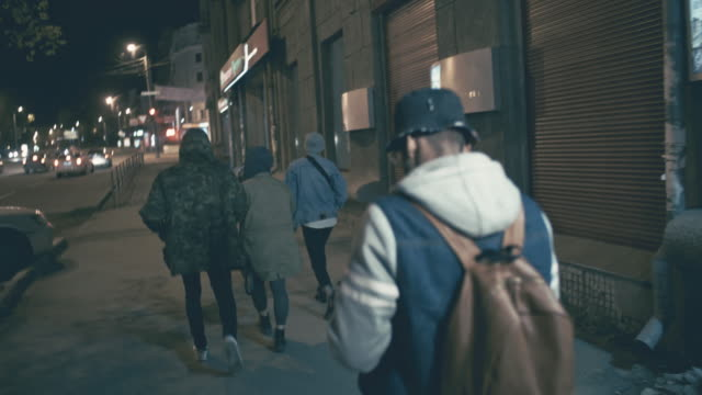 young people walking along street at night - junger erwachsener stock-videos und b-roll-filmmaterial
