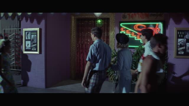 vídeos de stock e filmes b-roll de 1967 ms td pan young people walking and entering dance hall stam's cellar - camisa e gravata