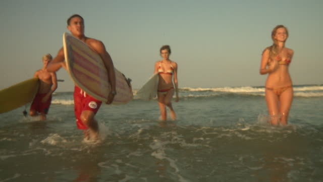 slo mo ms young people walking out of sea carrying surfboards, jacksonville, florida, usa - jacksonville florida stock videos and b-roll footage