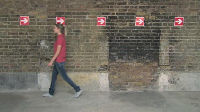 Young people walking past arrows on wall one by one